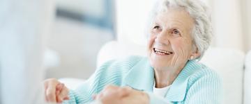 Oudere dame kijkt iemand aan buiten het beeld